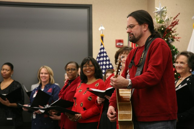 The Holiday Program Choir prepares for song, as led by Tim Jennings of the Future Warfare Center on the guitar.