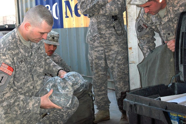 Sgt. David Shirley (left), a customs border clearance agent for the 150th Armored Reconnaissance Squadron, 30th Heavy Brigade Combat Team, inspects the contents of a footlocker, Dec. 11, for prohibited items, to ensure the Soldiers return home safely.