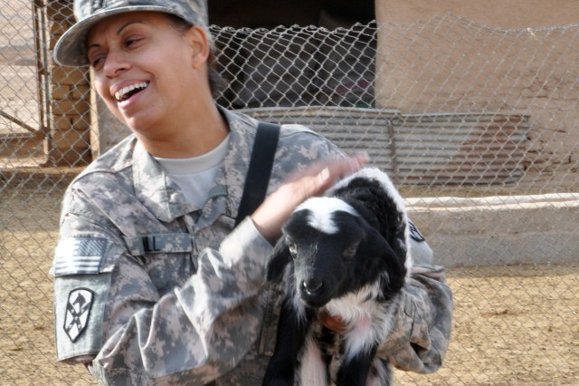 "Capt. Elaina Hill, a Fairbanks, Alaska, native, and the 15th Sust. Bde. adjutant, holds a lamb during a visit here by 15th Sust. Bde. leaders Dec. 16. ""When [Hussen Ismaiel Ahnd, Jedellah Sofla's mukhtar,] shoved that lamb [at me], he said, 'What's your name?' and I said 'baa?'"" Hill explained, laughing. (U.S. Army photo by Sgt. Matthew C. Cooley, 15th Sustainment Brigade public affairs)"