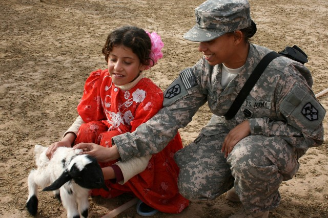 Capt. Elaina Hill, a Fairbanks, Alaska, native, and the 15th Sust. Bde. adjutant, pets a lamb with a local girl during a visit here by 15th Sust. Bde. leaders Dec. 16. (U.S. Army photo by Master Sgt. Celia Feller, 15th Sustainment Brigade)