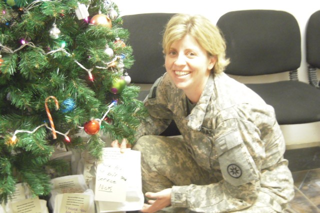 Capt. Amy Noble, the chaplain for the 395th Combat Sustainment Support Battalion, holds a care package placed underneath a Christmas tree at Contingency Operating Location Q-West, Iraq. (Courtesy photo)