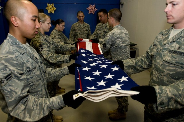 Service members in the Joint Base Balad Honor Guard execute a six-man flag fold during one of the team's bi-weekly practices at Joint Base Balad, Iraq.