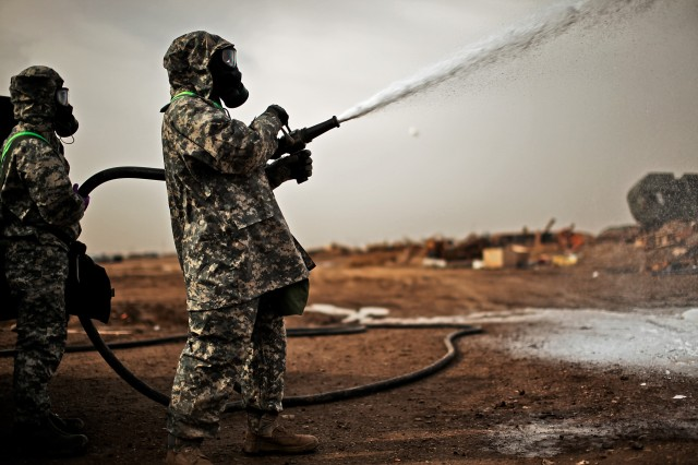 Two Soldiers from the 1st Air Cavalry Brigade, 1st Cavalry Division, work together to handle a highpressure hose during chemical, biological, radiological and nuclear training, here, Dec. 22. The Soldiers were learning the proper techniques to spray terrain and buildings with safety foam in the event of a CBRN incident.