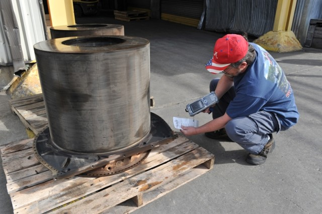 Using Automatic Identification Technology, Anthony Vinson, a materials expeditor in the Turbine Engine Value Stream at Anniston Army Depot, scans the routing tag for an engine matrix on its way to the welding shop for additional disassembly.