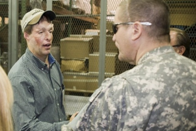 Master Sgt. Jeffrey Mittman, right, is greeted in the small arms repair facility at Anniston Army Depot by Johnathan Purser, a quality assurance specialist for the Directorate of Engineering and Quality who started working at the depot in 2006 under the Always a Soldier program.