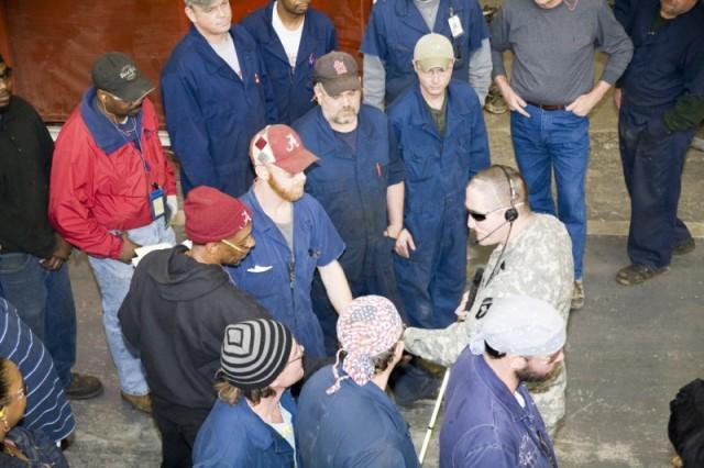 Mechanics and welders in Anniston Army Depot's Nichols Industrial Complex flock to Master Sgt. Jeffrey Mittman.