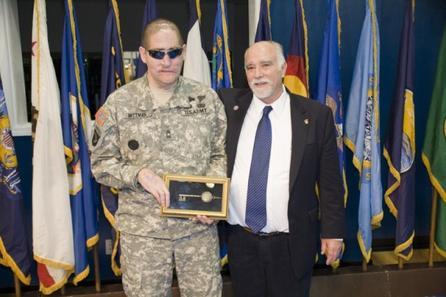 Anniston Mayor Gene Robinson presents Master Sgt. Jeffrey Mittman with a key to the city.