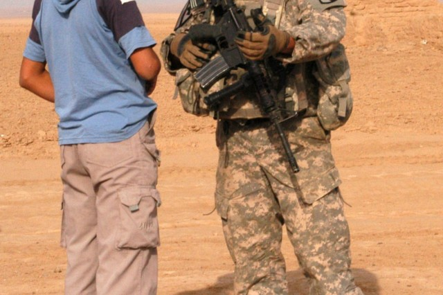 CONTINGENCY OPERATING LOCATION Q-WEST, Iraq - Sgt. Patrick A. Martin (right), a truck commander from Southaven, Miss., chats with an Iraqi boy outside the village of Ejbah who greeted the Soldiers during a presence patrol Dec. 15. Martin serves with the Mississippi Army National Guard's A Company, 2nd Battalion, 198th Combined Arms, 155th Brigade Combat Team, headquartered in Hernando, Miss. During the patrol, the Soldiers demonstrated their strategies for combating complacency, such as practicing battle drills, alternating routes and meeting with local Iraqis.