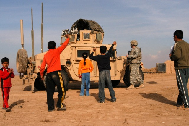 CONTINGENCY OPERATING LOCATION Q-WEST, Iraq - Children of Ejbah, a small village near Contingency Operating Location Q-West, greet members of the base force protection company during a presence patrol Dec. 15. The Soldiers serve with the Mississippi Army National Guard's A Company, 2nd Battalion, 198th Combined Arms, 155th Brigade Combat Team, headquartered in Hernando, Miss. During the patrol, the Soldiers demonstrated their strategies for combating complacency, such as practicing battle drills, alternating routes and meeting with local Iraqis.