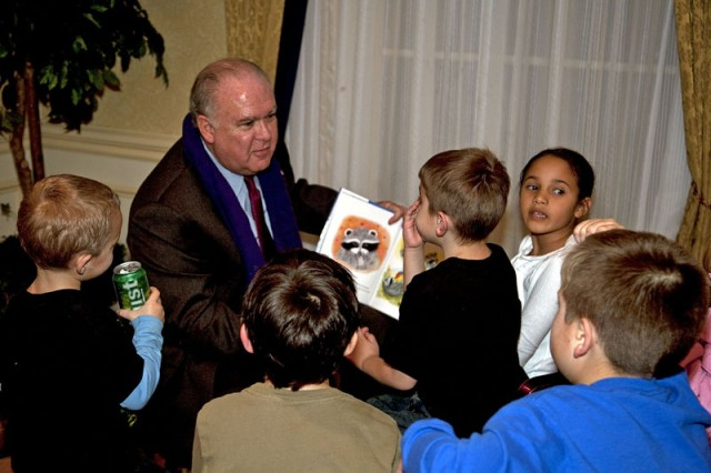 """Army Under Secretary Joseph Westphal reads to children attending an AUSA-sponsored holiday party at Walter Reed Army Medical Center's Mologne House. """"The Kissing Hand"""" by Audrey Penn was specially chosen from a reading program designed by the Military Child Education Coalition to spark healing conversations among families of the wounded."""