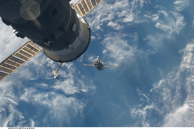The Soyuz TMA-17 spacecraft approaches the International Space Station, carrying Russian cosmonaut Oleg Kotov, NASA astronaut Col. T.J. Creamer and Japanese astronaut Soichi Noguchi. A docked Russian spacecraft is at top left.