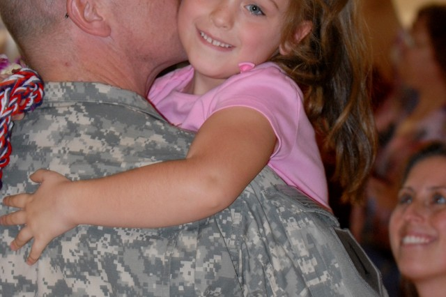 Five-year-old Lexey Amsdell is all smiles as she hugs her daddy, Cpt. Matthew Amsdell, 65th Engineer Battalion, during a redeployment ceremony at Wheeler Army Airfield, Hawaii, Dec. 19, as her mommy, Kelly, looks on. Amsdell and more than 340 Soldiers returned from a year-long deployment to Iraq just in time for the holidays.