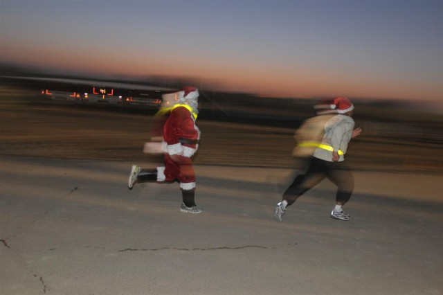Col. Fredrick Brown, assistant chief of staff for operations with the 13th Sustainment Command (Expeditionary), and Santa (Sgt. 1st Class Ryan Kohles, the noncommissioned officer in charge of Iraqi Security Forces linguists with the 13th ESC) sprint ahead of the pack to start the Reindeer Run 10K Dec. 19 at Joint Base Balad, Iraq.