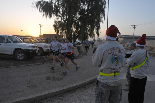 Volunteers from the 13th Sustainment Command (Expeditionary) cheer for participants during the Reindeer Run 10K Dec. 19 at Joint Base Balad, Iraq.