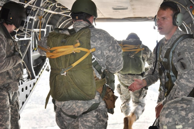 Staff Sgt. Phillip Alderson (right) acts as the safety jumpmaster for paratroopers from his unit as they leave the helicopter during a static line jump at 1,500 feet.