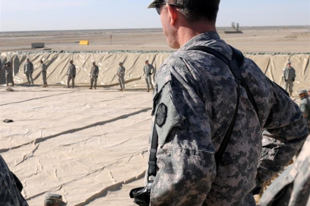 Brig. Gen. Paul L. Wentz, commanding general of the 13th Sustainment Command (Expeditionary) out of Fort Hood, Texas, watches as Soldiers roll out the bags for the fuel farm Dec. 21 during his visit to Contingency Operating Location Adder, Iraq. Wentz said the Adder fuel farm is scheduled to be completed in March, and all convoy operations for the area will be conducted there after Cedar II is emptied of fuel and closed as part of the upcoming drawdown of U.S. forces and equipment from Iraq.