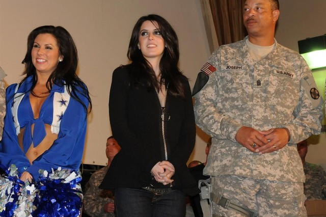 Justine Phillips, a Dallas Cowboy cheerleader, musician Alana Grace and Command Sgt. Maj. Mark D. Joseph, with the 13th Sustainment Command (Expeditionary) out of Fort Hood, Texas, listen to the Army Band, Downrange, perform at the Sustainer Theater Dec. 19 at Joint Base Balad, Iraq. The United Service Organization tour traveled to Kuwait, Iraq and Afghanistan during the holiday season.