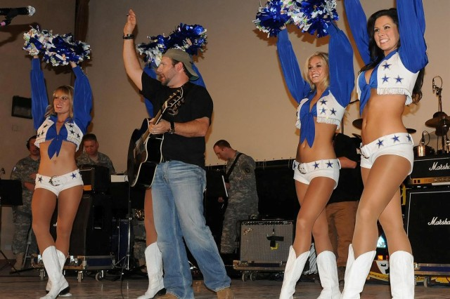 Country musician Mark Wills and four Dallas Cowboys cheerleaders thank the crowd for attending the Sergeant Major of the Army Hope and Freedom Tour 2009, at the Sustainer Theater Dec. 19 at Joint Base Balad, Iraq. The USO tour traveled to Kuwait, Iraq and Afghanistan during the holiday season.