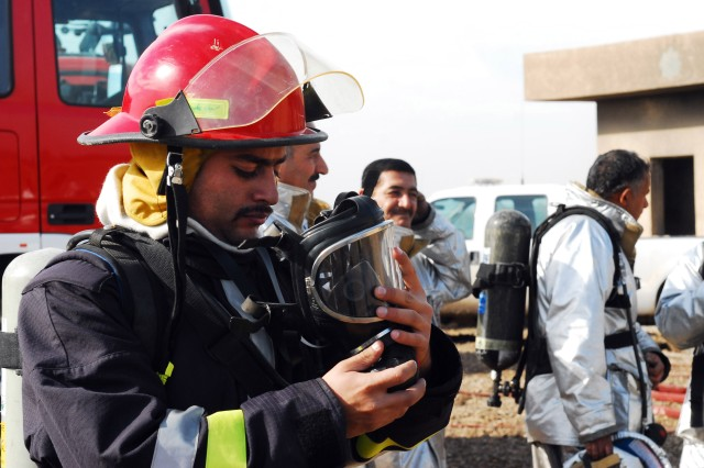 A fireman from the Iraqi Air Force secures the breathing regulator to his mask before entering the burn building during a joint training excercise with U.S. Air Force  and Baghdad International Airport firefighters.
