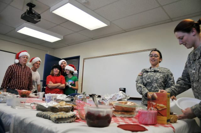 Company C, 229th Military Intelligence Battalion First Sergeant Micheal Dochterman's (far left) family and friends watch as Soldiers from his battalion receive food for their Christmas dinner this year.  Dochterman said he wanted to make sure the Soldiers had a home cooked meal since they had to be away from their families.