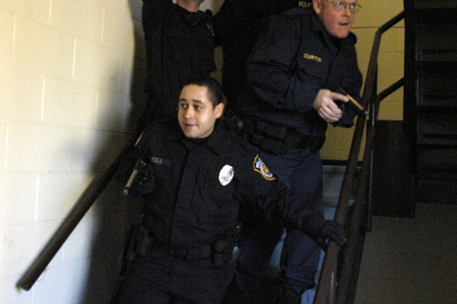 Officer Abe Vega of the Joint Base Myer-Henderson Hall police department holds down the rear as the group practices securing a stairway in the event of an active shooter
