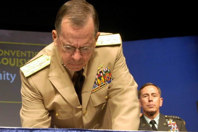 Chairman of the Joint Chiefs of Staff Adm. Michael Mullen signs the Army Community Covenant at the 91st National Convention of the American Legion in Louisville, Ky. Gen. David H. Petraeus, commander, U.S. Central Command, waits his turn to sign next.