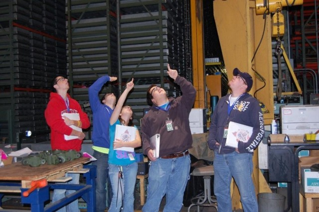 Students of RIA-JMTC's Logistics Academy look at a crane in building 210 during a class.