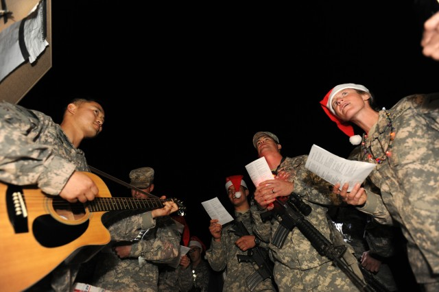 On a dark and not so silent night following a Christmas Eve chapel service, members of the Forward Operating Base Farah congregation and other base patrons who decided to join them, led by 4-73rd Calvary Chaplain, U.S. Army Capt. Light Shin with the 82nd Airborne Division, sing Christmas carols and hand out greetings cards to all U.S. Soldiers, Sailors, Airmen and Marines, Dec. 24, Farah, Afghanistan.