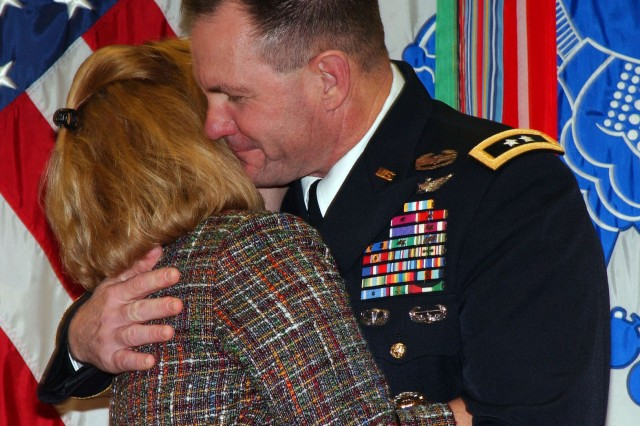 FORT SAM HOUSTON, Texas - Maj. Gen. Perry Wiggins (right), deputy commanding general, U.S. Army North, embraces his wife, Annette, after being promoted to major general during a promotion ceremony Dec. 28 inside Army North's historic headquarters at the Quadrangle.  Wiggins thanked his Family members for their support throughout the years and presented flowers to Annette; his mother, Beverly Wiggins; and Merella Warder, Annette's mother. Retired Lt. Gen. Freddy McFarren, former commanding general, U.S. Fifth Army, performed the honors of administering the oath of office for Wiggins during the ceremony.