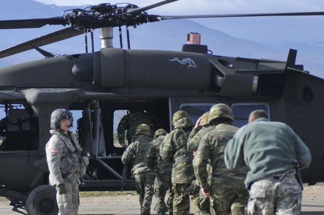Greek Soldiers board the UH-60 Blackhawk helicopter during hot/cold load training at Camp Rigas Fereos near Camp Bondsteel, Kosovo.Body
