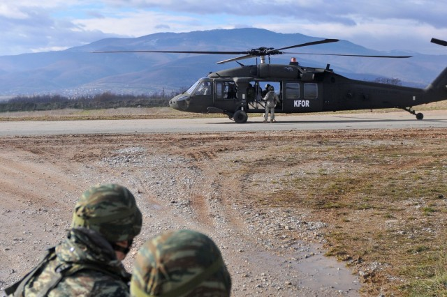 Greek Soldiers watch as the UH-60 Blackhawk helicopter prepares to depart during hot/cold load training at Camp Rigas Fereos near Camp Bondsteel, Kosovo.Body