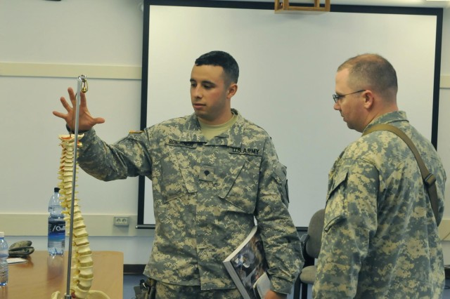"""U.S. KFOR Soldier Spc. Ricardo Roncancio, Corona, Calif., answers questions of fellow KFOR peacekeeper Spc. James V. Mann, Menifee, Calif., both of the 1-144th Maneuver Task Force, during a recent mock court trial, part of the """"Fundamentals of Criminal Law"""" class offered by the Laura Bush Education Center at Camp Bondsteel, Kosovo.ody"""