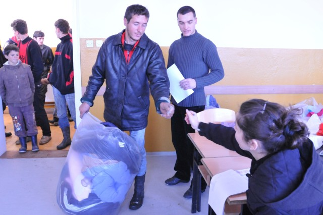 Selyete Zymeri, from the Albanian Red Cross, hands donated linens to a local from Novo Brdo, Kosovo, on Dec. 28, 2009. The linens were donated by MNTF-E Soldiers to families through a program coordinated by local non-government groups working with the Albanian Red Cross.Body