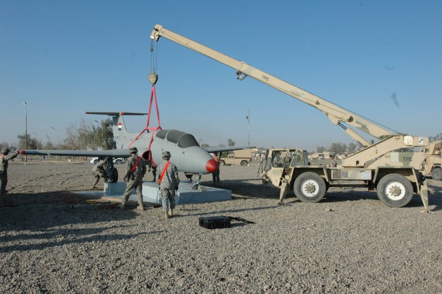 Soldiers of Company B, 209th Aviation Support Battalion, 25th Combat Aviation Brigade, Task Force Lobos, place a restored L-29 Delfin airplane at its final destination as a static display at Contingency Operating Base Speicher, outside of Tikrit, Iraq, Dec. 16.