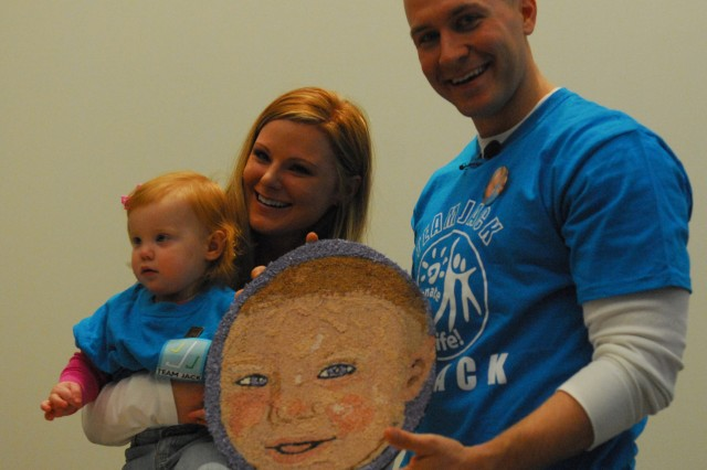 1st Lt. Eric Van Hecke, his wife Jennifer and daughter Lily of Monticello, Minn., display a floragraph, Dec. 23, of their son, Jack, who was a tissue donor in 2006. The floragraph, a memorial portrait made of floral materials, was part of the Donate Life float in the internationally televised Tournament of Roses Parade on New Year's Day.