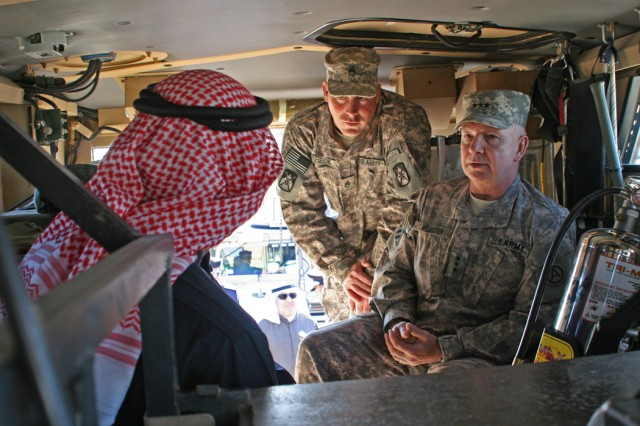 Lt. Gen. William G. Webster, U.S. Army Central commander and Soldiers from the 110th Transportation Company teach Kuwaiti officials about U.S. military vehicles that will be occupying a new road provided by the Kuwait government for U.S. military convoys. The brief lesson occurred shortly after a ribbon-cutting ceremony Dec. 30 to celebrate the completion of the road.
