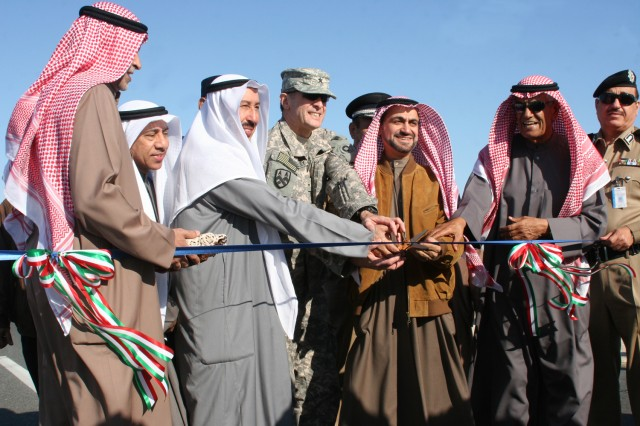 Brig. Gen. Mark MacCarley, deputy commander of the 1st Theater Sustainment Command, cuts a ribbon alongside Kuwaiti officials to celebrate the opening of a new military convoy route Dec. 30. The Kuwaiti government provided the road for U.S. servicemembers traveling between camps across Kuwait.