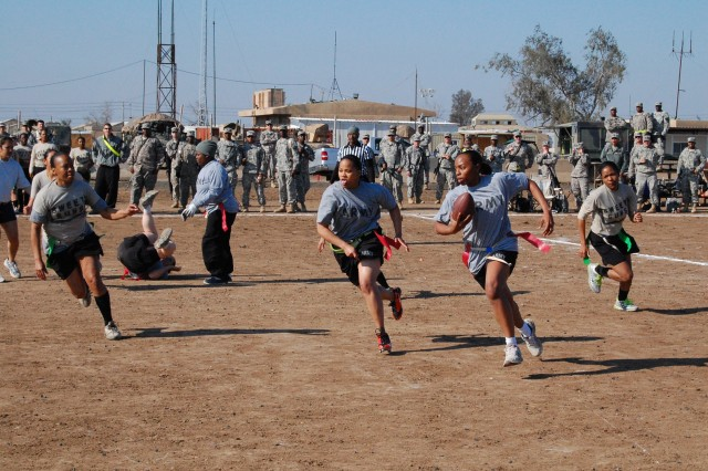 "CAMP TAJI, Iraq - Pago Pago, America Samoa native, Spc. Shusila Savae, a supply clerk for Headquarters and Headquarters Company, 1st Brigade Special Troops Battalion, 1st Brigade Combat Team, 1st Cavalry Division, blocks for Pfc. Jessica Cisero, a Tampa, Fla., native as she races towards the end zone for a touchdown against ""Sweet Guns"", the female Powder Puff Team from 4th Battalion, 227th Aviation Regiment, 1st Air Cav. Brigade, 1st Cav. Div.  The 1st BSTB Powder Puff Team won the game by 7 points."