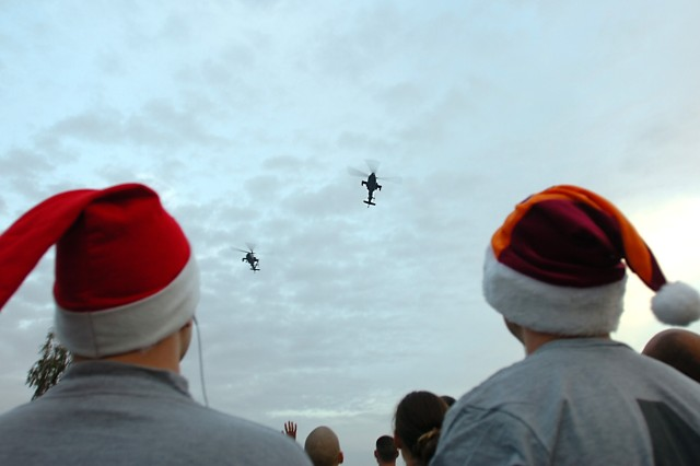 CAMP TAJI, Iraq - Two Soldiers watch as a pair of AH-64D Apache attack helicopters from 4th Battalion, 227th Aviation Regiment, 1st Air Cavalry Brigade, 1st Cavalry Division, perform a low flyover for runners before the kick-off of the 5K Jingle Bell Run, here, Dec. 25. The 4-227th Soldiers hosted the event to bring a little cheer to those away from family this holiday season and to share in the camaraderie of their military family, said Lt. Col. Randy Haws, of Vernal, Utah, commander, 4-227th.