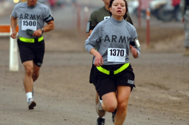 CAMP TAJI, Iraq- Capt. Traci Yamada, from Lakewood, Wash., battalion adjutant, 4th Battalion, 227th Aviation Regiment, 1st Air Cavalry Brigade, 1st Cavalry Division, finishes strongly down the final stretch on her way to winning the women's section of the 5K Jingle Bell Run, Dec. 25, here. The run was hosted by the 4-227th and attracted hundreds of competitors.