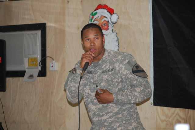 """BAGHDAD - Sgt. Taurus """"Mack"""" McDaniel, a cavalry scout from Kountze, Texas, performs his original song, """"Mr. Krashtown"""", during his solo act in a talent show held by the 1st Squadron, 7th Cavalry Regiment, 1st Brigade Combat Team, 1st Cavalry Division at Joint Security Station Istiqlaal, Dec. 21. Soldiers transformed the station's dining facility into a concert hall to entertain their fellow Troopers with """"Istiqlaal's Got Talent""""."""