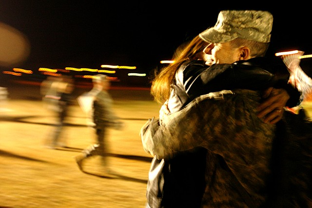 Sgt. 1st Class Jennifer Edwards, of Co. A, 15th Brigade Support Battalion, 2nd Brigade Combat Team, 1st Cavalry Division, kisses her husband, Sgt. 1st Class Jerald Edwards, of 2nd BCT Headquarters, as he and more than 100 others returned Dec. 26, from their deployment to Iraq