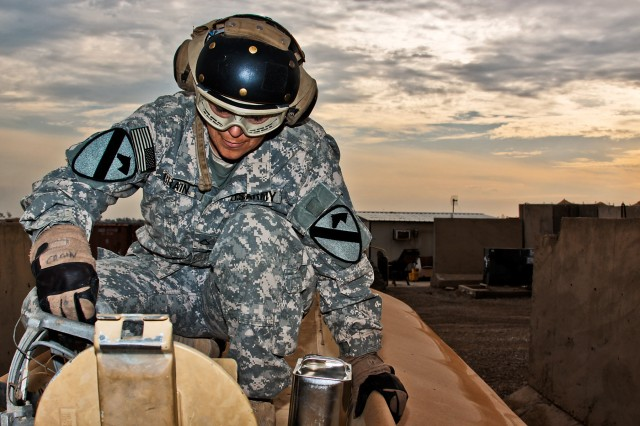 CAMP TAJI, Iraq - After stirring up the fuel, Pfc. Cindy Crain, from Kokomo, Ind., a fuel handler in Company A, 615th Aviation Support Battalion, 1st Air Cavalry Brigade, 1st Cavalry Division, pulls a fuel sample for testing in the petroleum lab, here, Dec. 29.