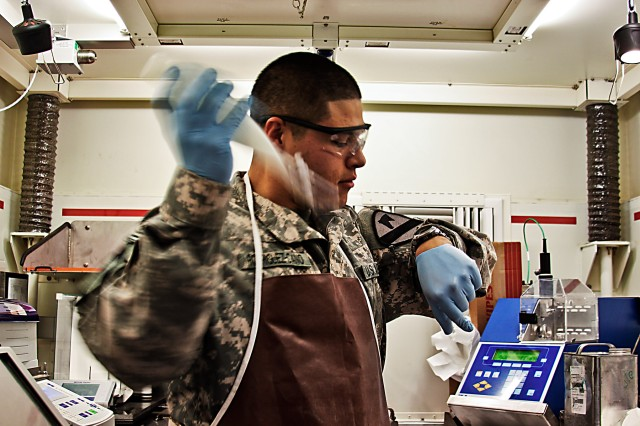 CAMP TAJI, Iraq - During a fuel sample test, Spc. Juan Rodriguez-Cano, from Edinburg, Texas, a petroleum lab technician, in Company A, 615th Aviation Support Battalion, 1st Air Cavalry Brigade, 1st Cavalry Division, shakes a mixture of chemicals and fuel for five minutes to determine the level of additives in the fuel, here, Dec. 29. The lab has reached its 1,000th test, representing over 40 million gallons tested.