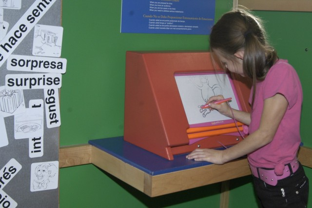 Andrea draws out her emotions on the Magna Doodle in the playhouse of the Emotions Matter exhibit. The exhibit has been dismantled at Ft. Lewis and is currently being stored at the Children's Museum of Tacoma, awaiting it's next trip to another