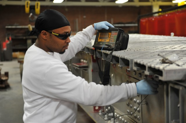 Welder Phillip Swain uses an ultrasonic tester to check a bridge panel at Anniston Army Depot.
