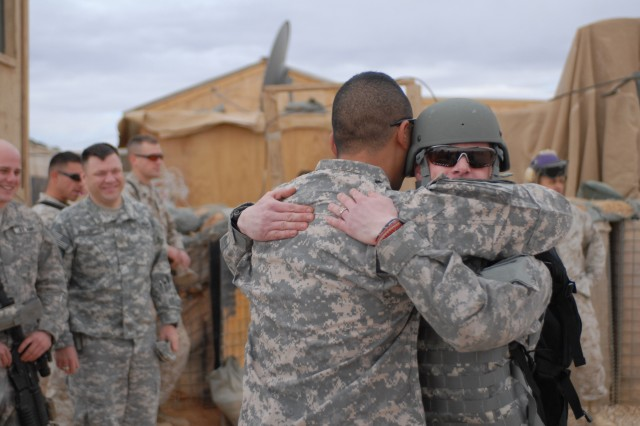 Sgt. Bill Congleton (right) hugs Staff Sgt. Jesse Parks, Oregon National Guard, as Congleton arrives at Camp Korean Village Dec. 29. Parks and Congleton served together in Iraq in 2004 when Congleton was struck by an improvised explosive device that resulted in a below-the-knee amputation.