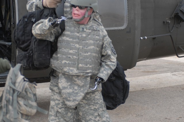 Capt. Sam Brown (rear) helps Sgt. 1st Class Mike Schlitz with his backpack as they exit a UH-60 helicopter at Camp Korean Village, Iraq, Dec. 29. The Soldiers spent the day visiting troops in western Iraq as part of Operation Proper Exit, a program designed to give injured combat veterans a chance at finding closure after they were injured.