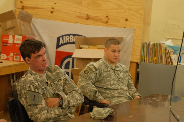 Capt. Sam Brown (left) tells his story to Soldiers from the 82nd Airborne Division Dec. 29, at Camp Ramadi in Iraq. Brown was injured in Afghanistan in 2008 when he was struck by an improvied explosive device. He suffered third degree burns to 30 percent of his body, and took part in Operation Proper Exit in order to tell troops about his experiences as a wounded warrior.
