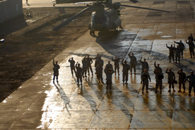 Soldiers from 1st Air Cavalry Brigade, 1st Cavalry Division, wave bye to five wounded warriors Dec. 31, as they depart Camp Taji, Iraq. The Soldiers spent a week visiting places throughout Iraq where they suffered life-altering injuries.